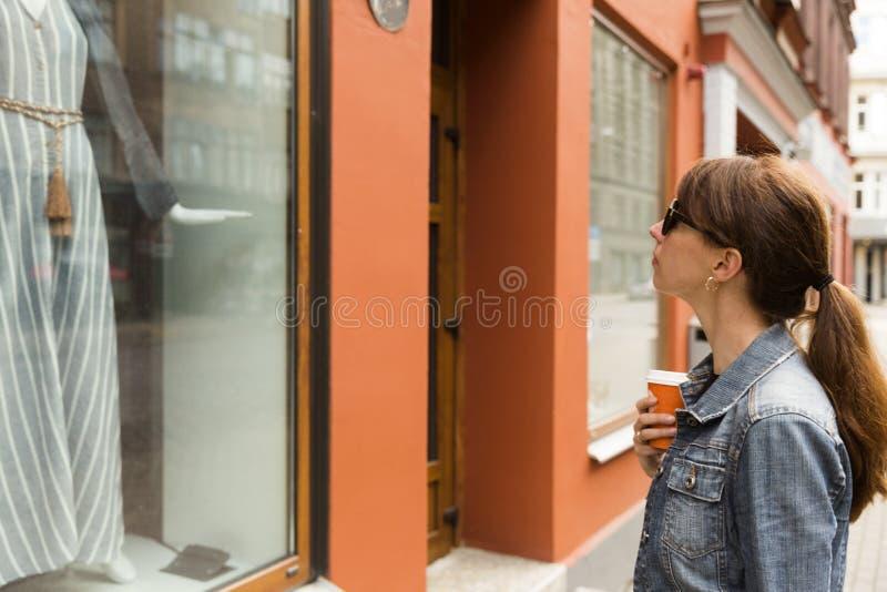 Concetto di acquisto della finestra Giovane donna che esamina vestito in una finestra del negozio fotografia stock