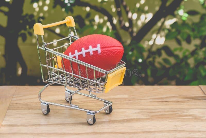 Concetto di acquisto: Giocattolo rosso della palla di rugby per i bambini nella mini regolazione gialla del carrello del supermer immagine stock libera da diritti