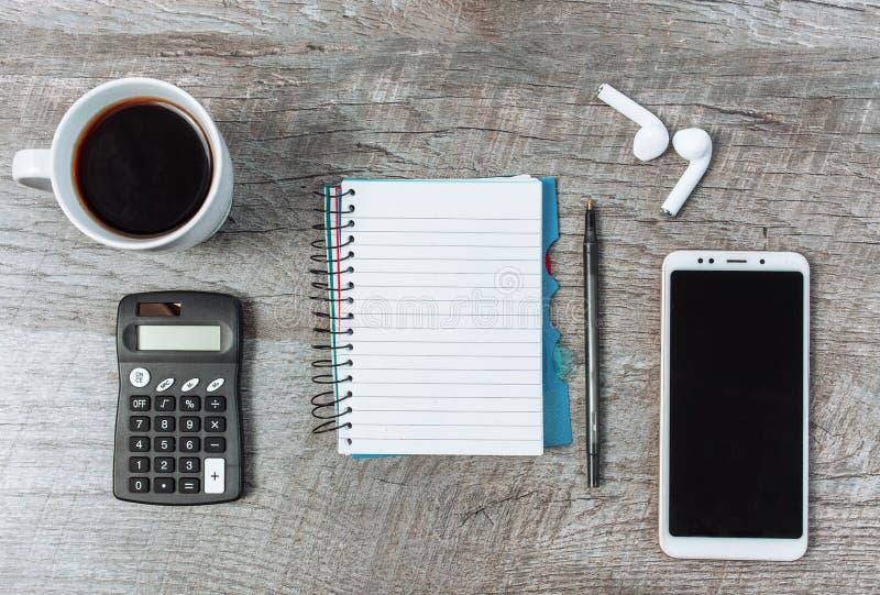 Concetto di affari, blocco note in bianco, smartphone e caffè, sull'corteggiare fotografia stock