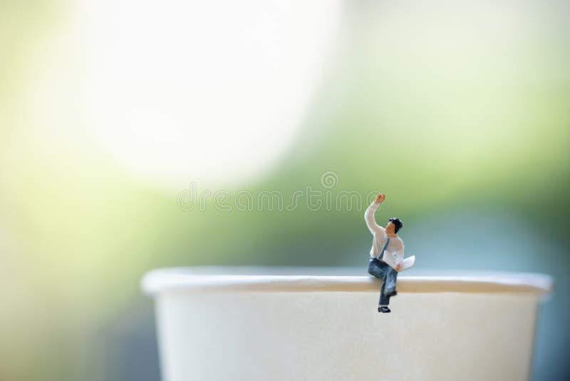 Concetto di affari Chiuda su della figura miniatura seduta dell'uomo d'affari e legga un giornale su per portare via la tazza di  fotografia stock