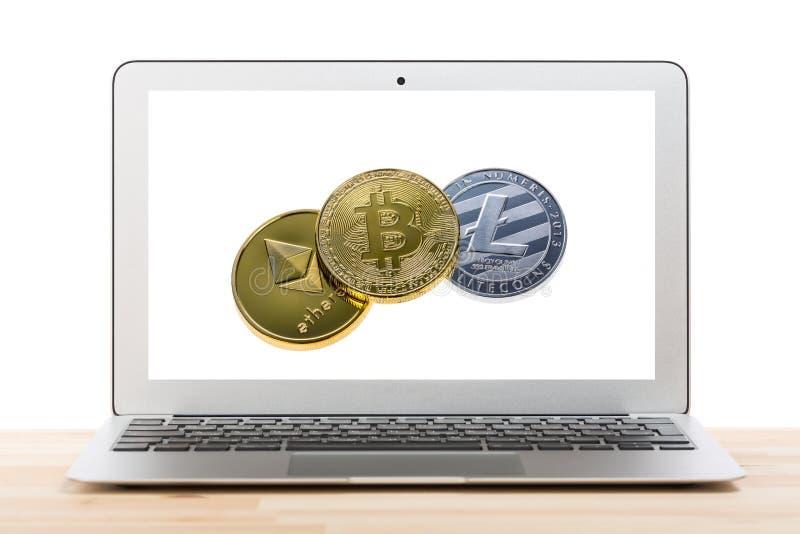 Concetto di affari di Cryptocurrency Computer portatile con bitcoin, litecoin e il ethereum sull'esposizione sulla tavola di legn fotografia stock libera da diritti