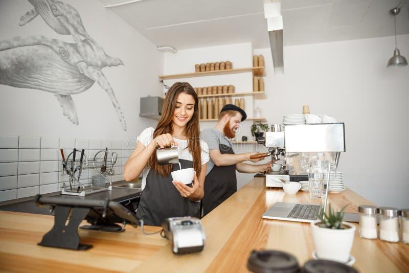 Concetto di affari del caffè - barista di signora del primo piano in latte preparante e di versamento del grembiule nella tazza c fotografia stock