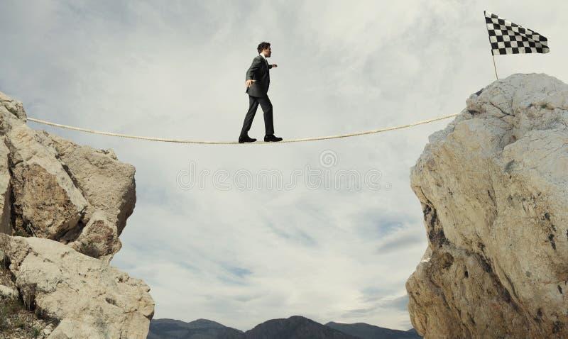 Concetto di affari dell'uomo d'affari che supera i problemi che raggiungono la bandiera su una corda fotografia stock libera da diritti