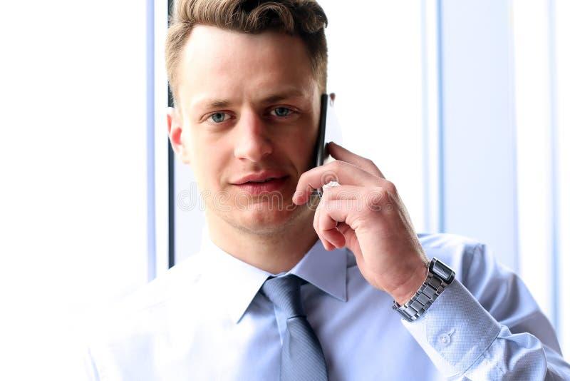 Concetto di affari, della gente e dell'ufficio - giovane uomo d'affari che rivolge allo smartphone sopra l'ufficio vicino con la  fotografia stock