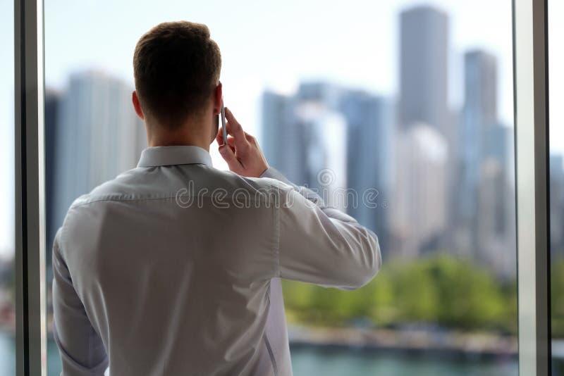 Concetto di affari, della gente e dell'ufficio - uomo d'affari che rivolge allo Smart Phone sopra l'ufficio vicino con la finestr fotografie stock