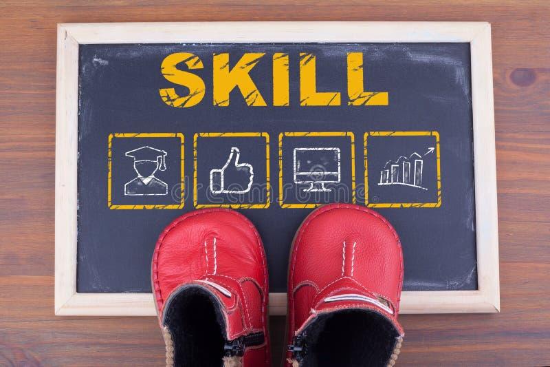 Concetto di affari di abilità e scarpe del bambino sopra sulla lavagna e sul backgroundr di legno immagini stock