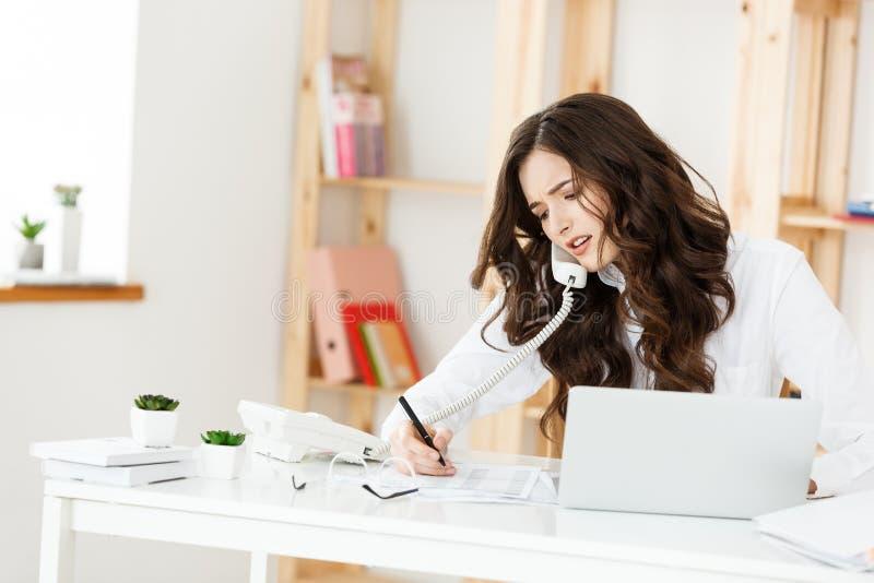 Concetto di affari: Donna di affari sveglia Unsmiling e seria che telefona nell'ufficio moderno luminoso fotografia stock