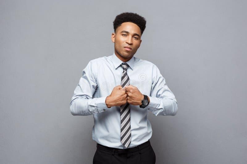 Concetto di affari - giovane afroamericano allegro sicuro in poseture di pugilato sopra fondo grigio immagini stock