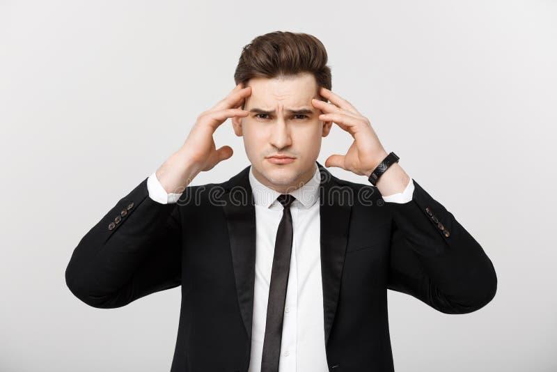 Concetto di affari: Giovane uomo d'affari con tenersi per mano sulla testa con espressione facciale di emicrania isolata sopra bi fotografie stock