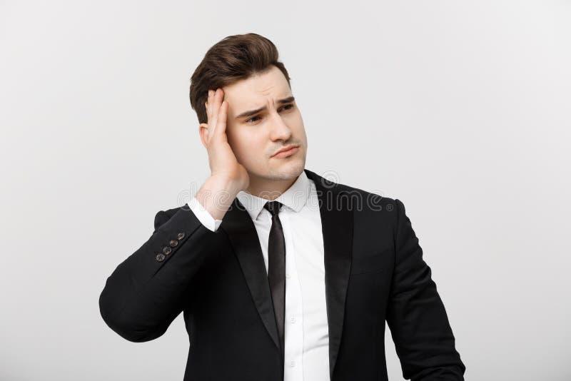 Concetto di affari: Giovane uomo d'affari con tenersi per mano sulla testa con espressione facciale di emicrania isolata sopra bi immagini stock libere da diritti