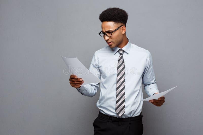 Concetto di affari - il giovane uomo d'affari afroamericano professionale bello ha concentrato la lettura sulla carta del documen fotografia stock