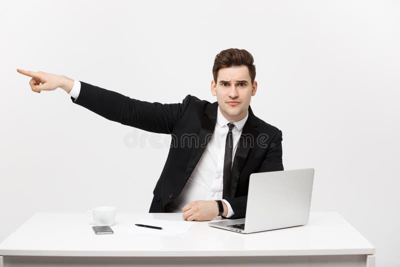 Concetto di affari: Il ritratto dell'uomo d'affari bello si è vestito in vestito che si siede nell'ufficio che indica il dito all fotografia stock
