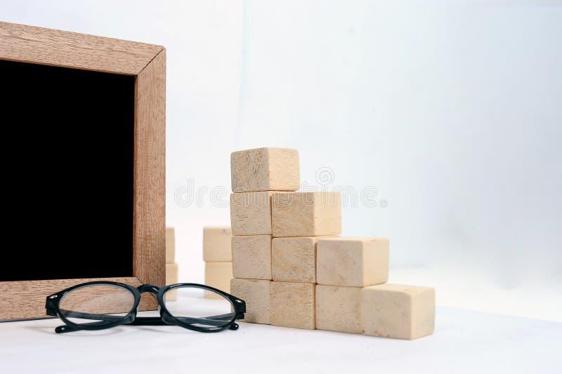 Concetto di affari per il processo di successo di crescita Blocco di legno che impila come scala di punto Vetri e lavagna fotografia stock libera da diritti