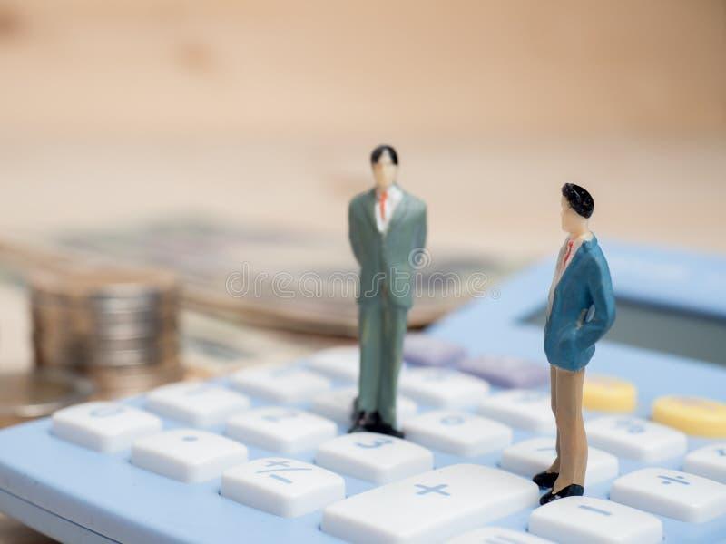 Concetto di affari piccole figure dell'uomo d'affari che stanno sul calcula immagini stock