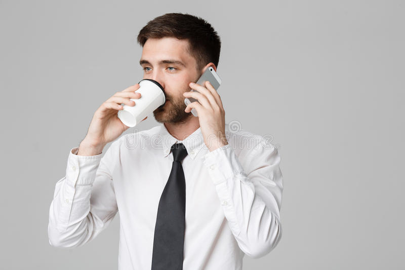 Concetto di affari - ritratto di un uomo d'affari bello in occhiali con una tazza di caffè e uno smartphone fotografia stock