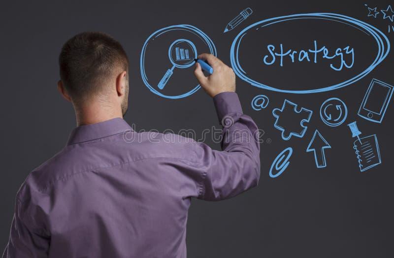 Concetto di affari, di tecnologia, di Internet e della rete Un giovane uomo d'affari scrive sulla lavagna la parola: Strategia immagini stock