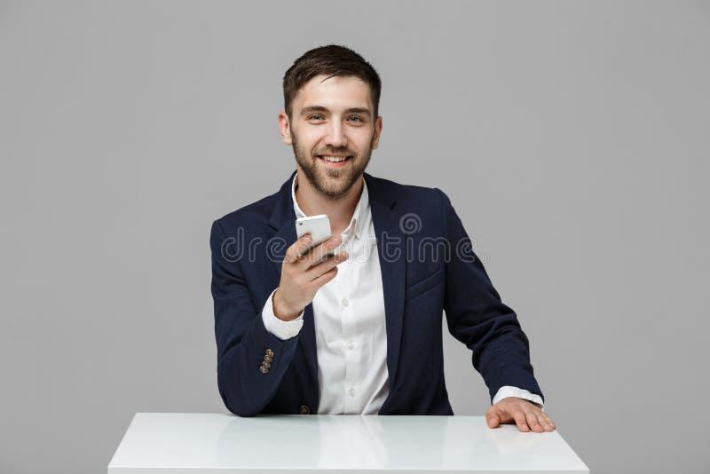 Concetto di affari - uomo bello di affari del ritratto che gioca telefono con il fronte sicuro sorridente Priorità bassa bianca C fotografia stock