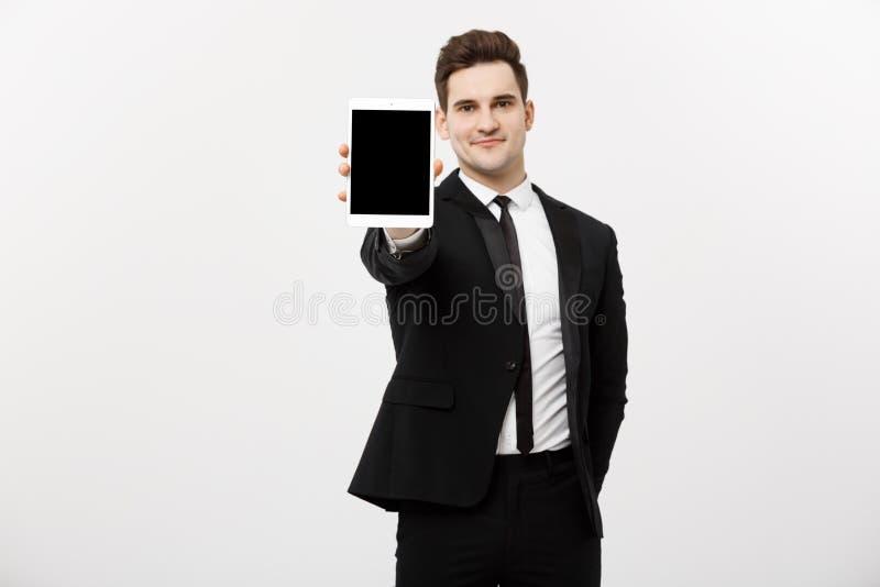 Concetto di affari: Uomo d'affari bello sorridente che presenta sito Web o presentazione sulla compressa fotografia stock