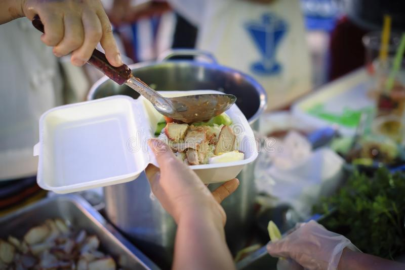 Concetto di alimentazione: I volontari danno l'alimento al povero: donare l'alimento sta aiutando gli amici umani nella società:  fotografia stock