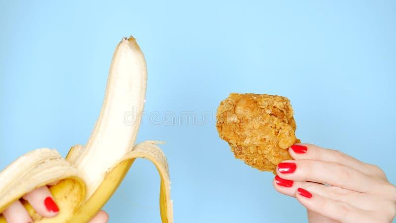 Concetto di alimento sano e non sano banana contro la coscia di pollo impanata fritta su un fondo blu luminoso femmina fotografia stock libera da diritti