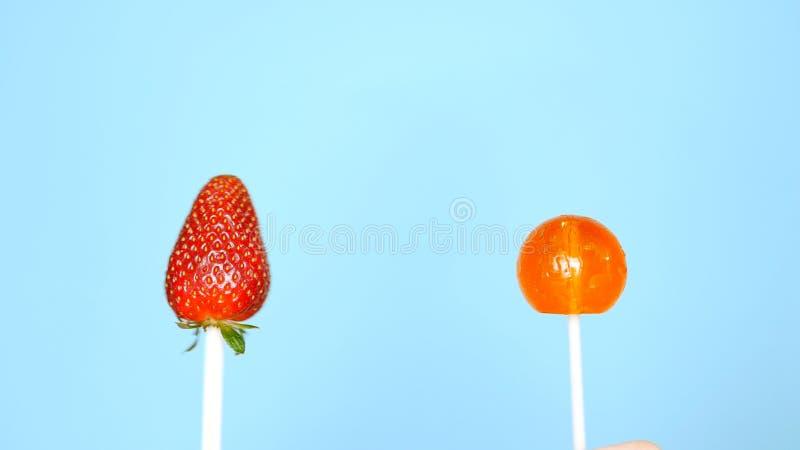 Concetto di alimento sano e non sano fragola contro la caramella su un fondo blu luminoso fotografia stock