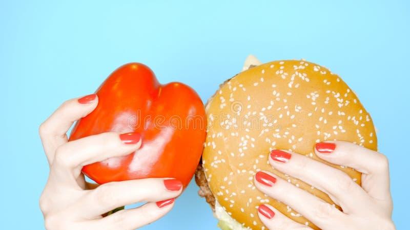 Concetto di alimento sano e non sano peperone dolce contro gli hamburger su un fondo blu luminoso Mani femminili immagine stock