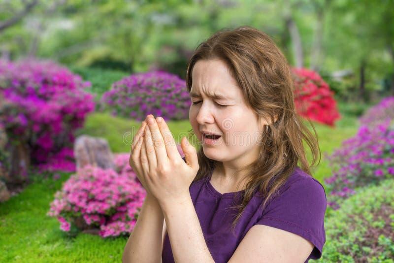 Concetto di allergia del polline La giovane donna sta andando starnutire Fiori nel fondo fotografia stock