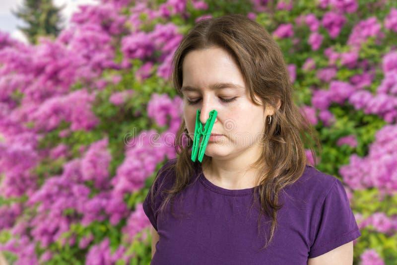 Concetto di allergia del polline La sopraelevazione ferroviaria della giovane donna respira e piolo d'uso sul suo naso immagine stock
