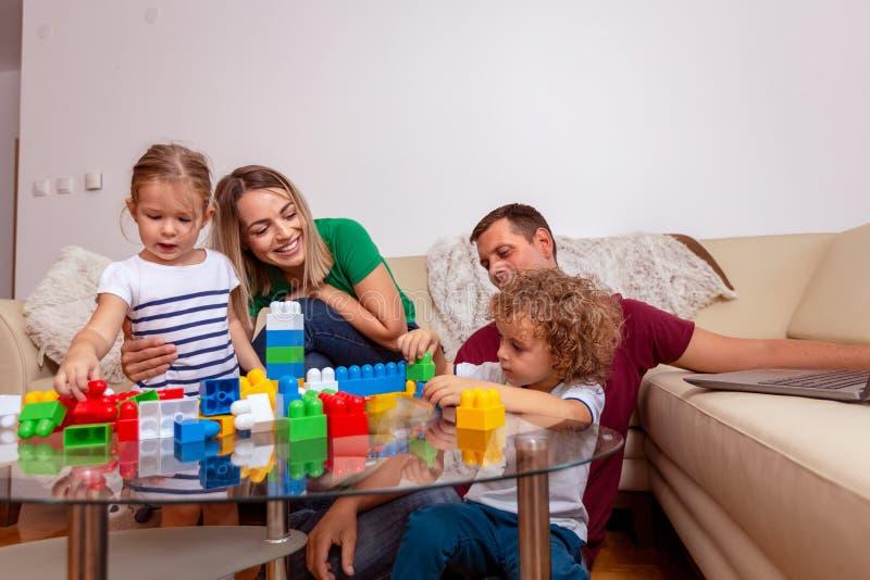 Concetto di amore della famiglia - Uomo e donna sorridenti che giocano con i bambini a casa immagini stock