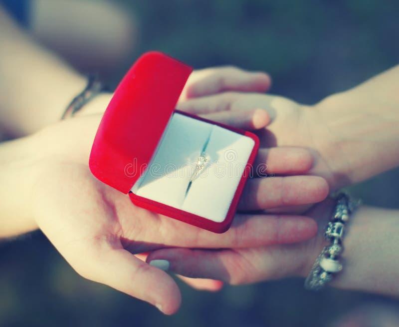 Concetto di amore, di impegno e di nozze - le mani coppia l'anello di fissaggio immagine stock libera da diritti