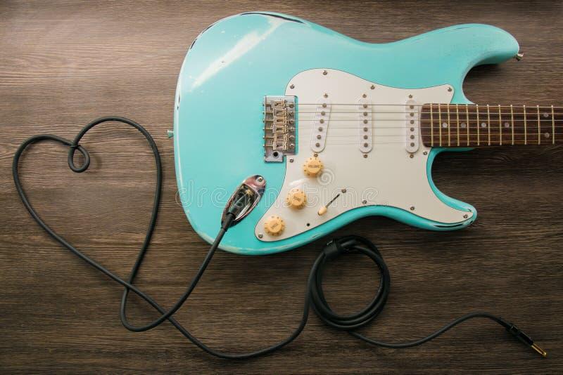 Concetto di amore di musica Chitarra del cuore della presa del cavo Chitarra elettrica blu-chiaro in una struttura di legno immagini stock libere da diritti