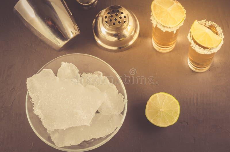 Concetto di Antivari: Colpi di tequila, calce, ghiaccio ed agitatore/colpi di tequila, calce, ghiaccio ed agitatore su un fondo s fotografia stock
