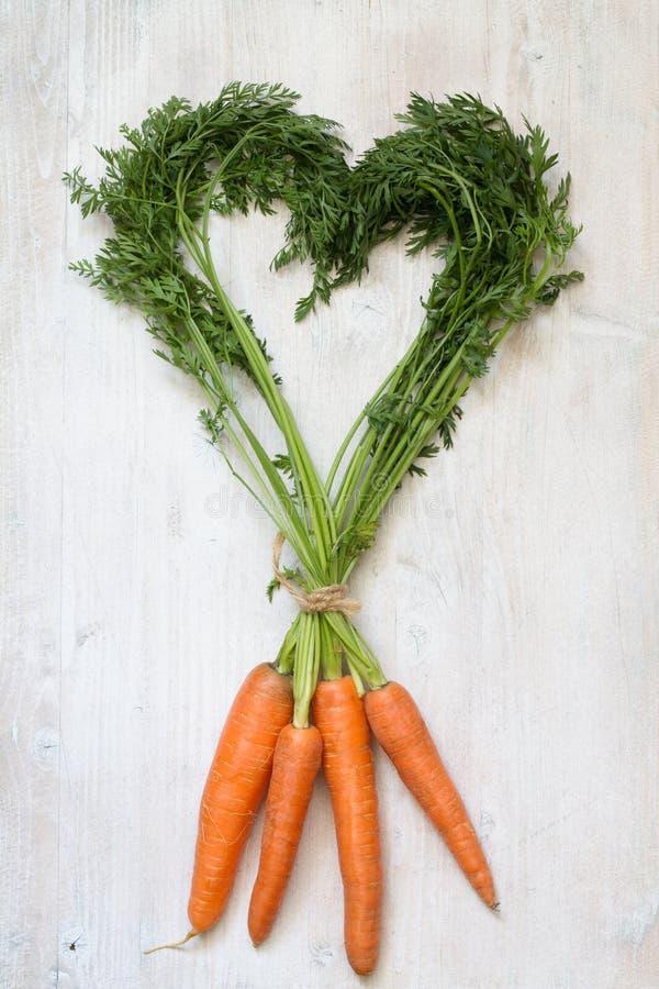 Concetto di arte di dieta sana del fondo dell'estratto di forma del cuore della carota fotografia stock