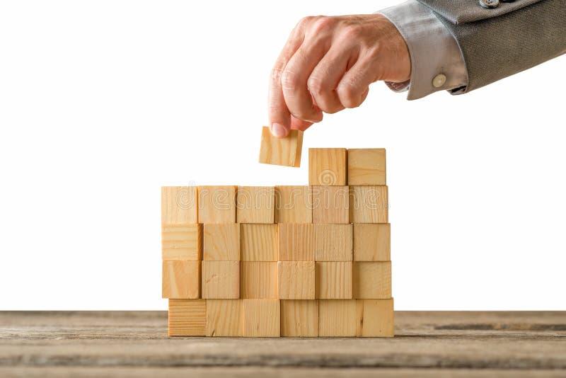 concetto di assieme di forme geometriche la mano di un uomo su un tavolo di legno fotografia stock libera da diritti
