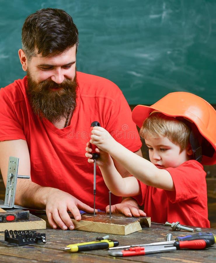 Concetto di assistenza e di lavoro di squadra Generi, parent con la barba che insegna al piccolo figlio ad utilizzare il cacciavi immagine stock