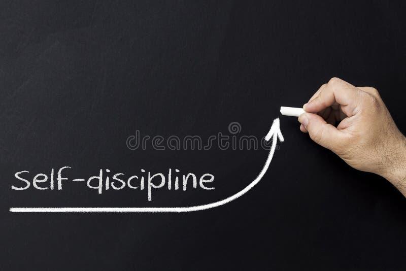 Concetto di autodisciplina Mano con la freccia in aumento del disegno di gesso Motivazione di auto e di disciplina immagini stock