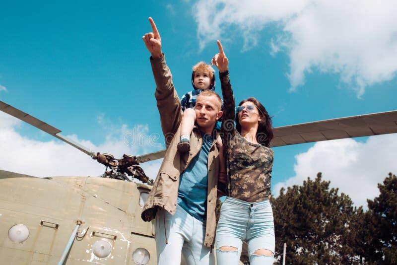 Concetto di avventura Dita del punto della famiglia all'elicottero Il piccolo figlio gode dell'avventura dell'estate con i genito fotografie stock