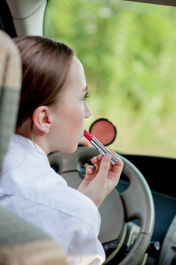 Concetto di azionamento del pericolo Adolescente dai capelli rossi del driver della giovane donna che dipinge le sue labbra che f fotografia stock