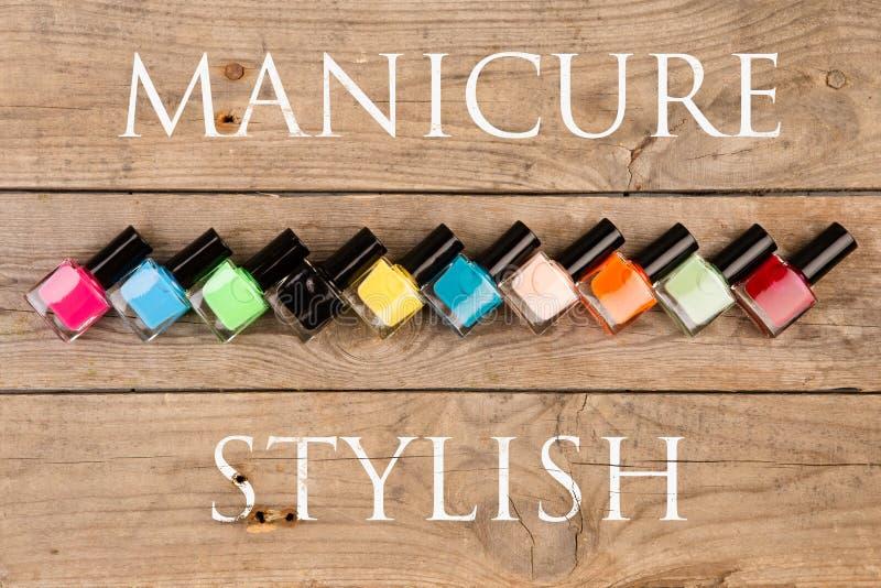 Concetto di bellezza - bottiglie variopinte luminose con gel-vernice per riguardare le unghie ed il manicure del testo alla moda immagini stock libere da diritti