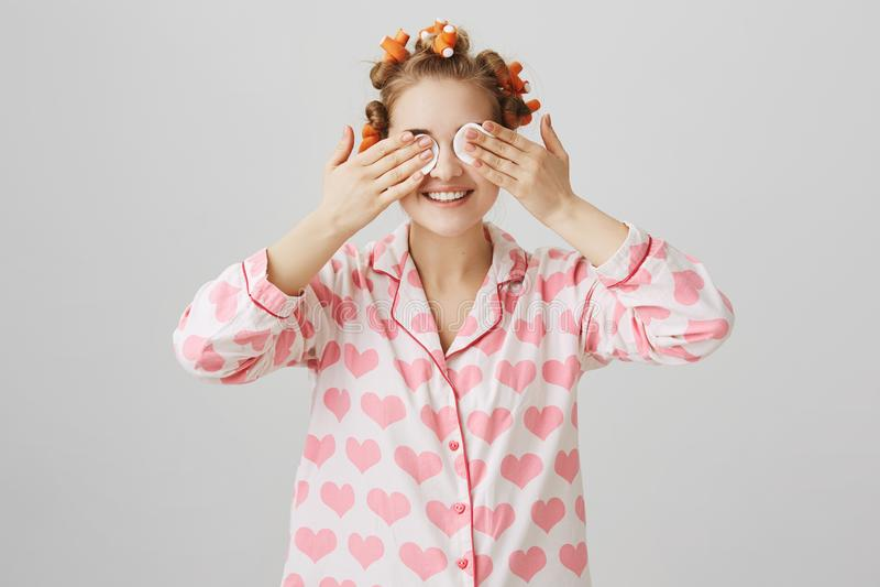 Concetto di bellezza e di comodità Ritratto della giovane donna affascinante con i bigodini che tengono i cuscinetti di cotone su immagine stock