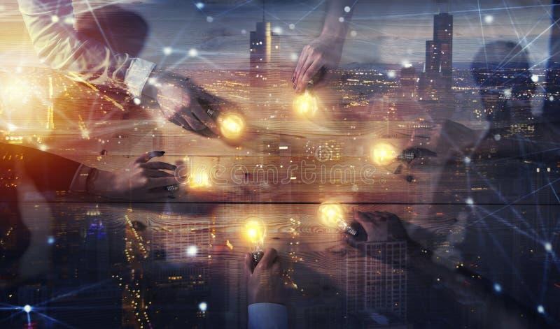 Concetto di 'brainstorming' e di lavoro di squadra con gli uomini d'affari che dividono un'idea con una lampada Concetto della pa immagini stock libere da diritti