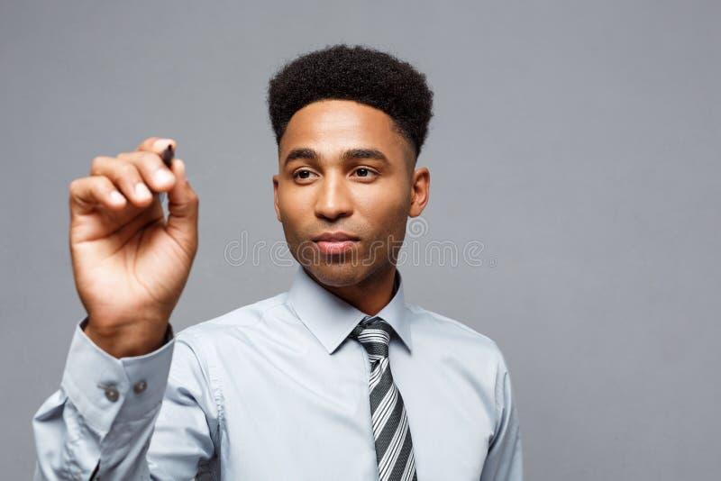 Concetto di Businsss - direttore aziendale afroamericano sicuro pronto a scrivere sul bordo o sul vetro virtuale in ufficio fotografia stock libera da diritti