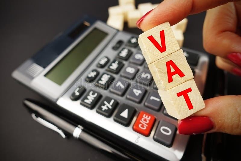 Concetto di calcolo dell'IVA con la parola del tino della tenuta della mano della donna sui cubi di legno sopra la tastiera del c fotografia stock libera da diritti