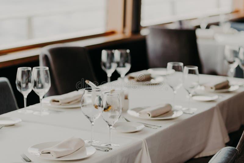 Concetto di celebrazione e di approvvigionamento Tavola di cena servita festiva con i vetri e la coltelleria sul tablewear bianco immagine stock libera da diritti