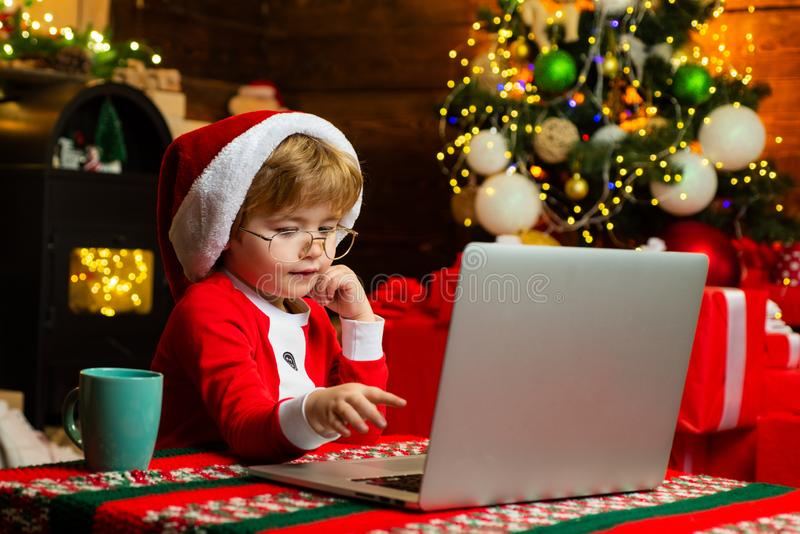 Concetto di compera di Natale Servizio dei regali Piccolo assistente di Santa Internet praticante il surfing del bambino astuto C immagini stock libere da diritti