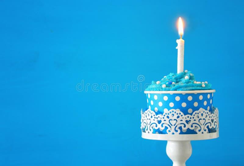 Concetto di compleanno con il bigné ed una candela sulla tavola di legno immagini stock