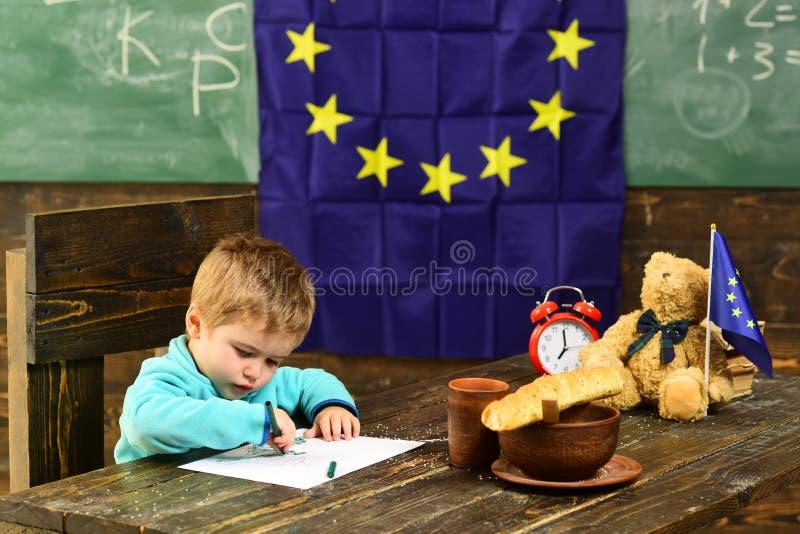 Concetto di conoscenza Tiraggio alla tavola con la bandiera dell'Eu sulla lavagna della classe, conoscenza del bambino Affamato p immagine stock libera da diritti