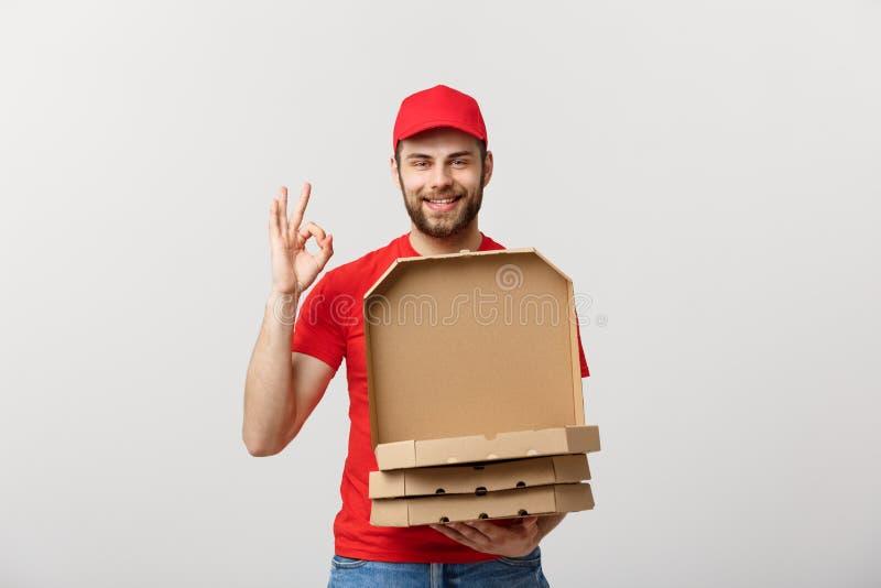 Concetto di consegna: Fattorino bello della pizza che fa segno GIUSTO isolato sopra fondo grigio fotografia stock