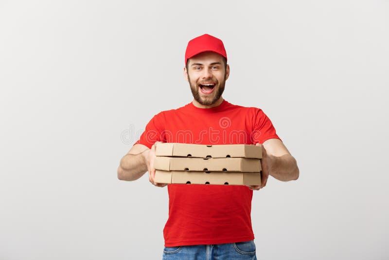 Concetto di consegna: Giovani contenitori bei caucasici di pizza della tenuta del fattorino della pizza isolati sopra fondo grigi immagini stock