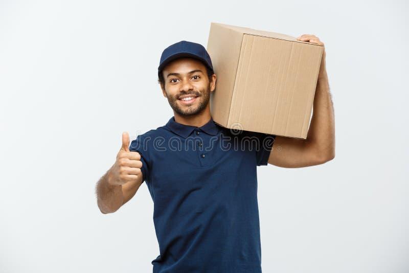 Concetto di consegna - il ritratto del fattorino afroamericano felice che tiene un pacchetto della scatola e che mostra si batte  immagini stock